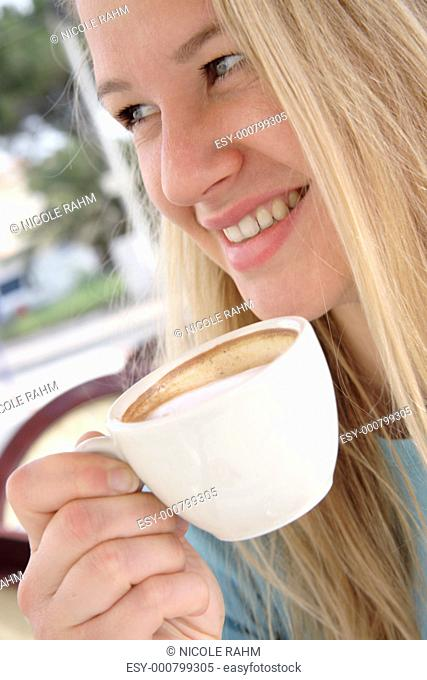 Young blond woman drinking cappuccino in a cafe, side view