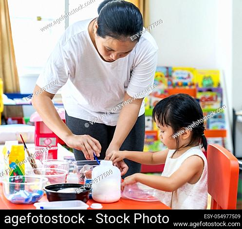 Asian girl kid playing toy and colorful paper for art lesson at living room in home as home schooling while city lockdown because of covid-19 pandemic across...