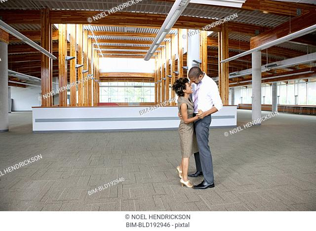 Couple dancing in empty office space