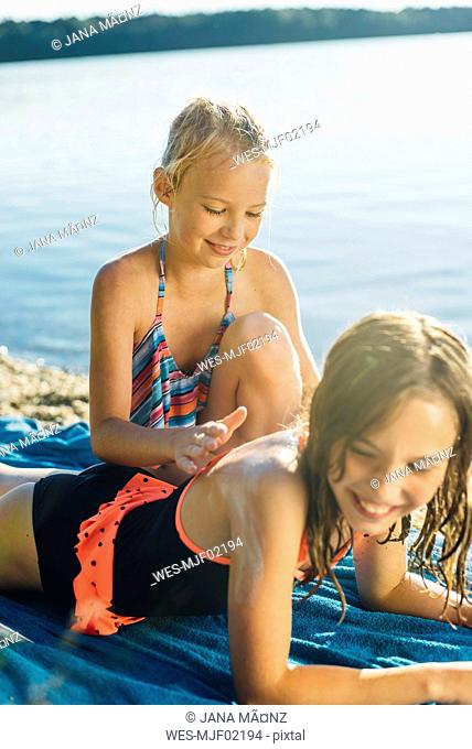 Girl applying sunscreen on shoulder of her friend on the beach