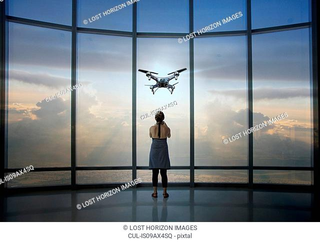 Full length rear view of woman watching drone from skyscraper window