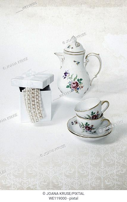 two vintage coffee cups, a coffee pot and a present box with a pearl necklace