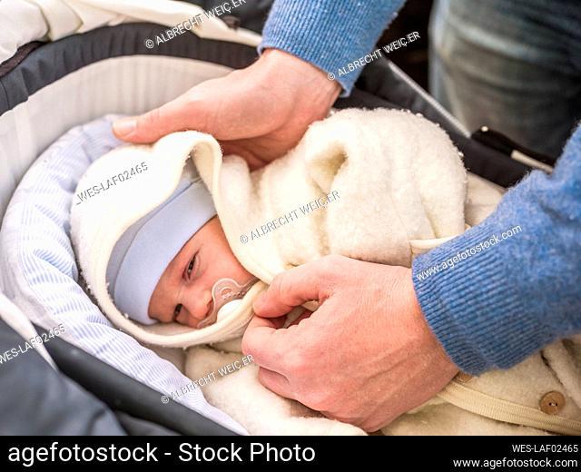 Father putting her newborn baby boy into pram