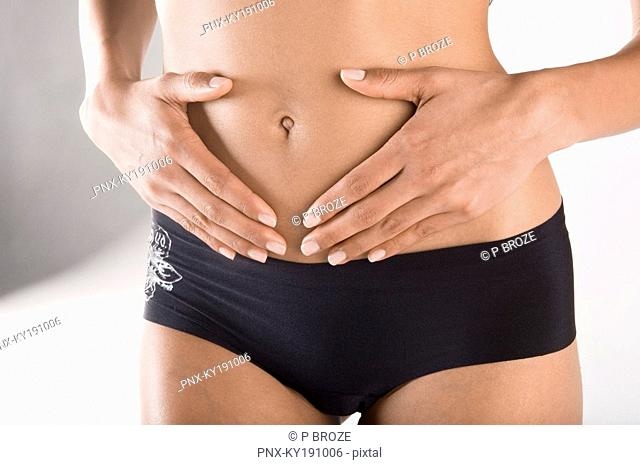 Mid section view of a woman touching her abdomen