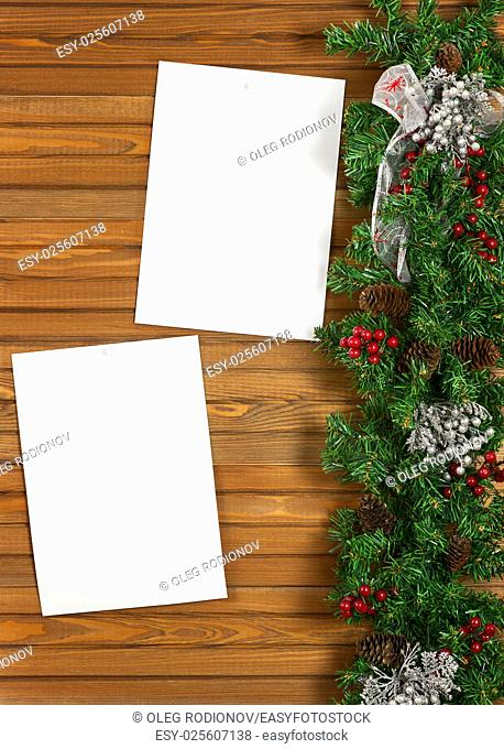 Garland with Christmas ornaments, pine cones and sheets of paper on wooden background