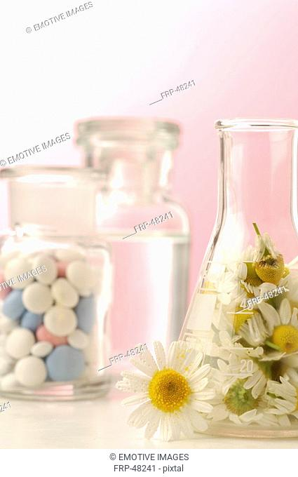 Camomile blossoms and pills in a bottle