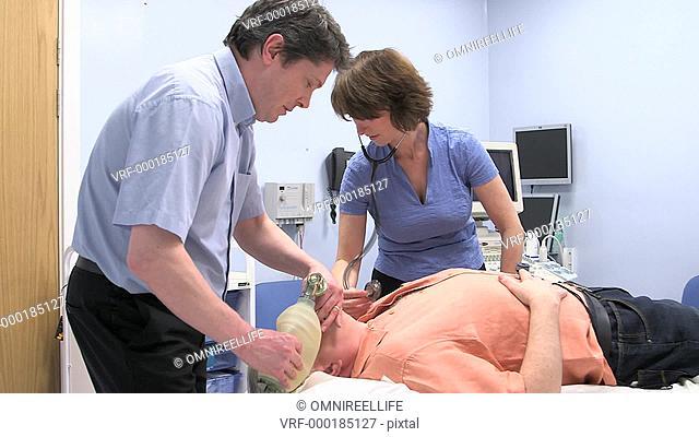 PAN WS Doctor and nurse resuscitating senior man