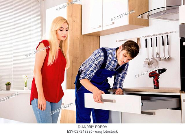 Male Worker Repairing Or Installing Drawer With Young Woman Standing In Kitchen