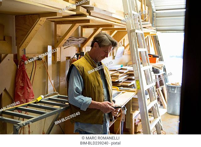 Caucasian carpenter texting on cell phone in workshop