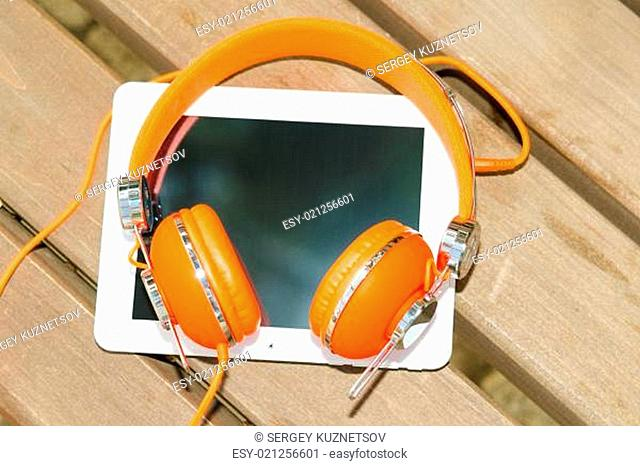White tablet PC with orange headphones on the wood bench