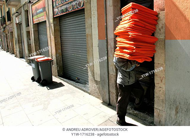 Man carrying cushions. Raval district, Barcelona, Spain