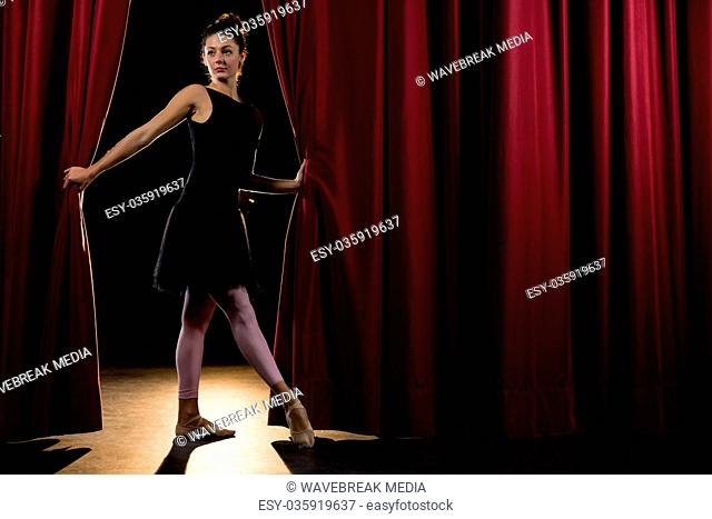 Ballerina posing in front of massive red stage curtain