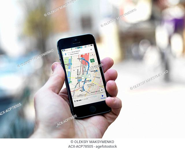 Person hand with iPhone displaying Google maps GPS navigator on streets of Tokyo, Japan