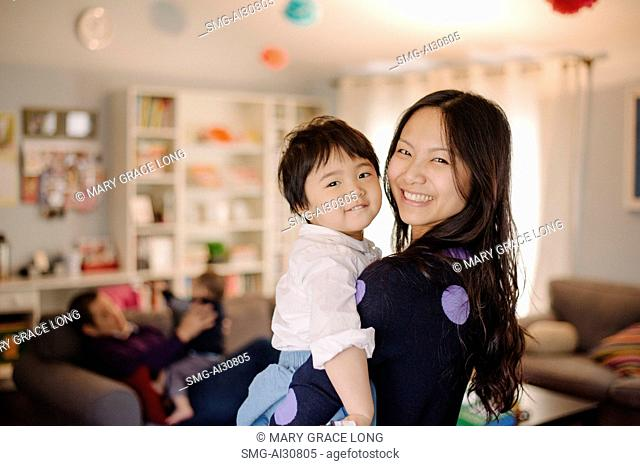 USA, Portrait of young woman carrying daughter (2-3)