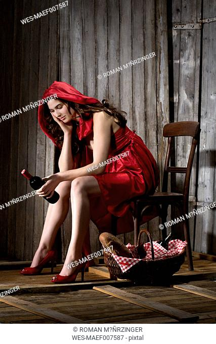 Young woman sitting in a shack dressed as Red Riding Hood, studio shot