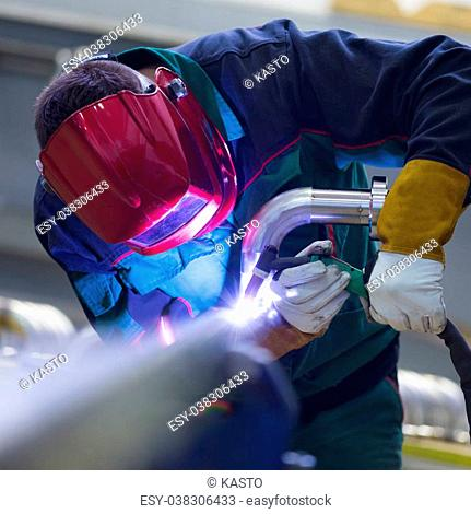 Industrial worker with protective mask welding inox elements in steel structures manufacture workshop