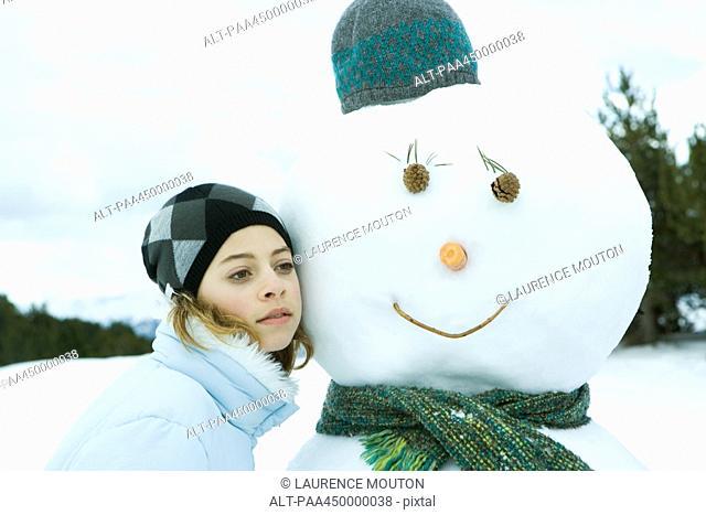 Teenage girl leaning against snowman, cheek to cheek, portrait