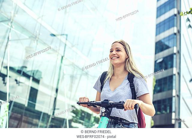 Portrait of laughing young woman with E-Scooter in the city, Berlin, Germany
