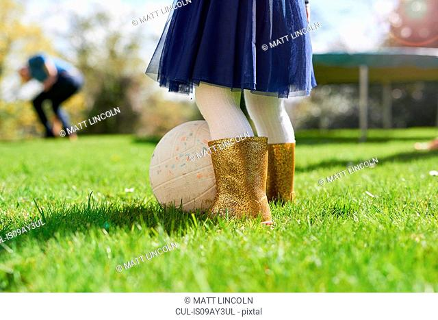 Low section of girl wearing sparkly wellington boots playing with ball