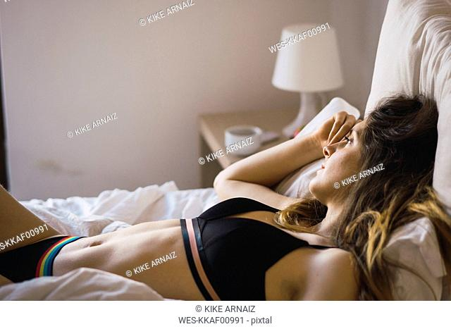 Daydreaming young woman in underwear lying on bed