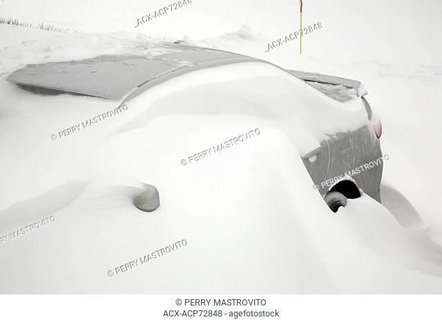 Gray car buried in snow during a snowstorm in winter, Laval, Quebec, Canada