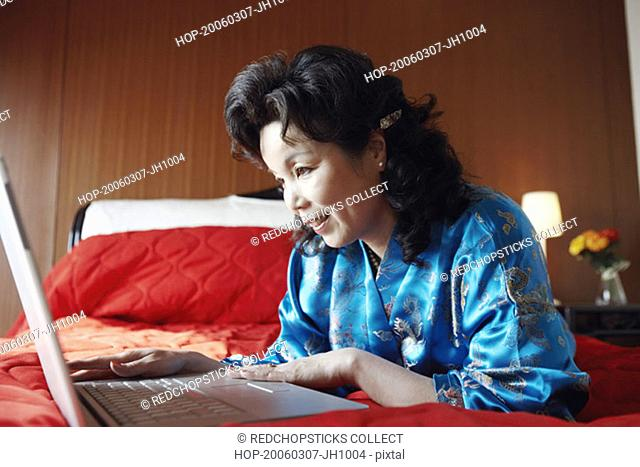Close-up of a mature woman sitting on the bed using a laptop