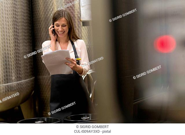 Young woman in wine cellar next to fermentation tanks, using mobile phone
