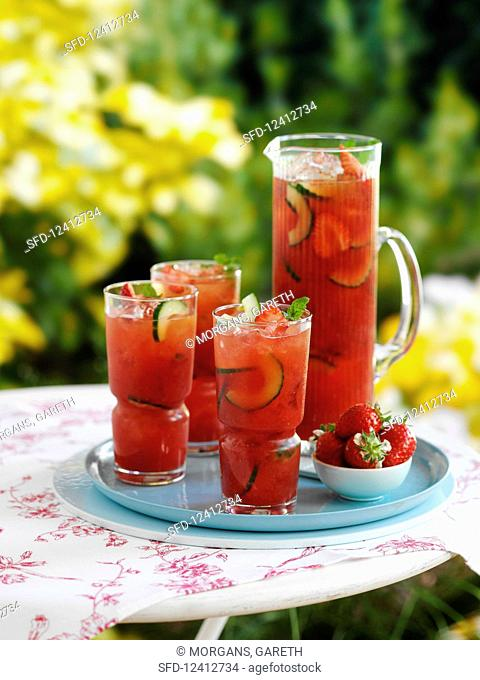 Iced tea in glasses with cucumbers and strawberries