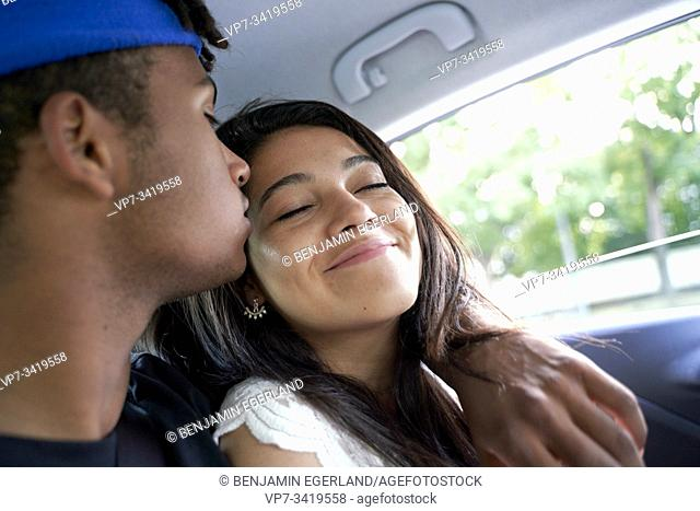 Young couple sitting together in the back seat of car