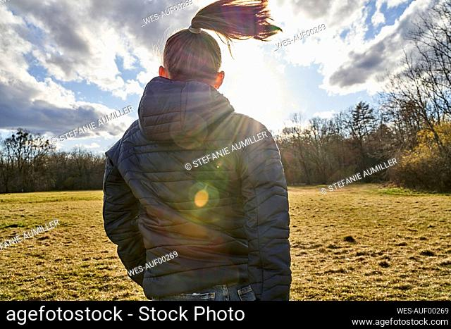 Rear view of girl moving on a meadow