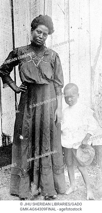 African-American mother standing with her young son, outdoors in front of a wooden wall in a farm setting, the mother standing with a hand on her hip and a...