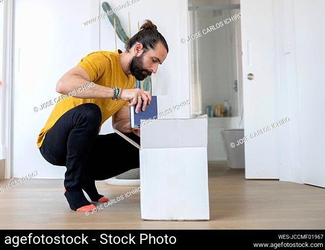 Man keeping book in cardboard box at home