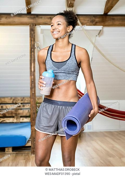 Smiling young woman holding yoga mat and healthy drink