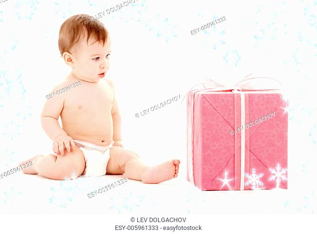 picture of baby boy in diaper with big gift box and snowflakes
