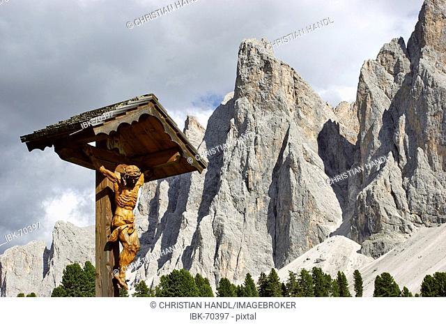 Wooden croos at the Gschnagenhardt alp behind the Geisler mountain range South Tyrol Italy