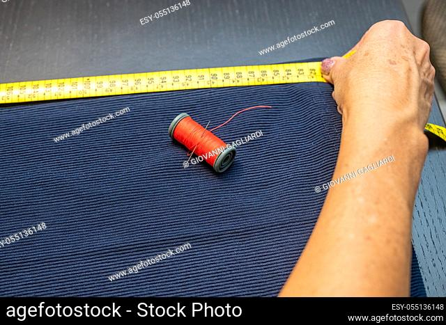 Female tailor working on a clothing sewing stitching measuring with yellow meter