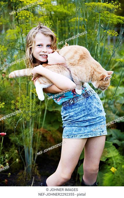 Girl holding cat in vegetable garden