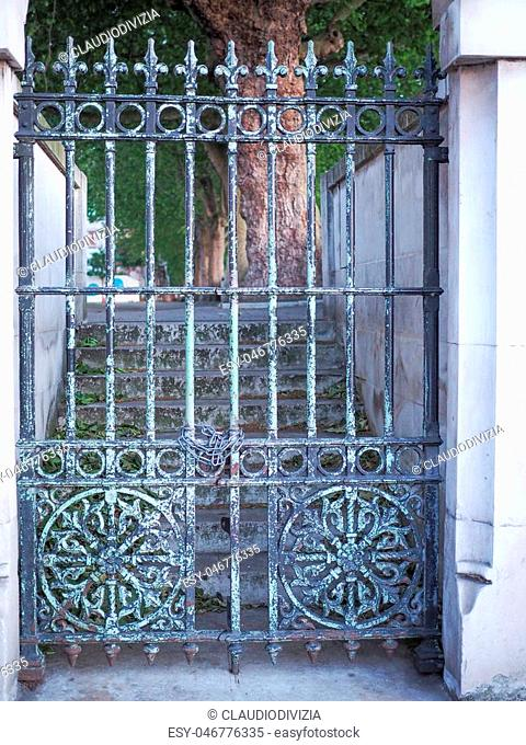 Old iron gate under a marble arch