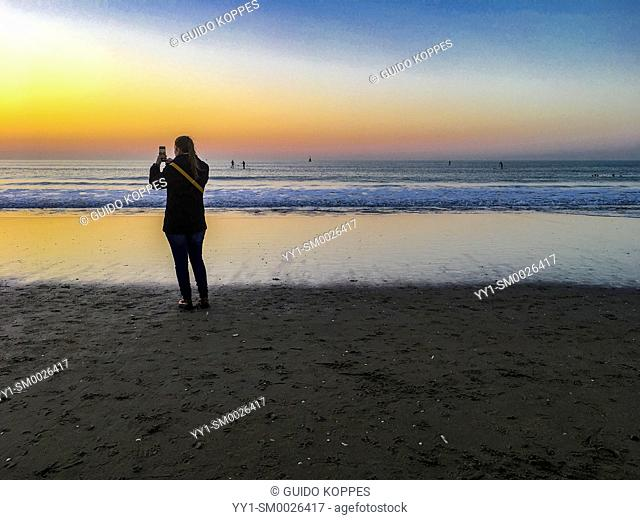 The Hague, Scheveningen, Netherlands. Young adult woman enjoying and capturing a beautifull sunset on the North Sea Beach during a warm