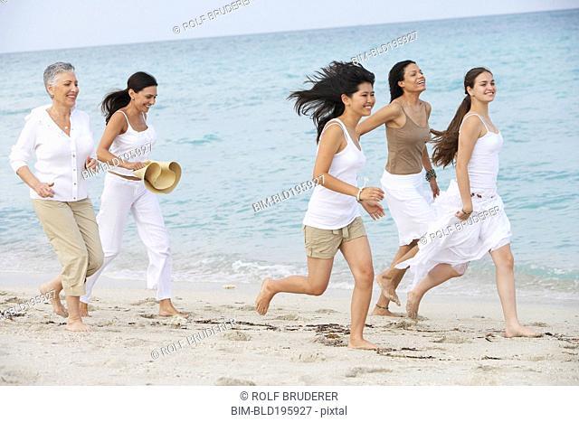 Diverse women running on beach together