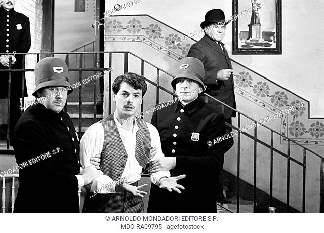 Italian actor Michele Placido held by two guards in The Black Hand. Behind him is American actor Lionel Stander as lieutenant Joe Petrosino. 1973