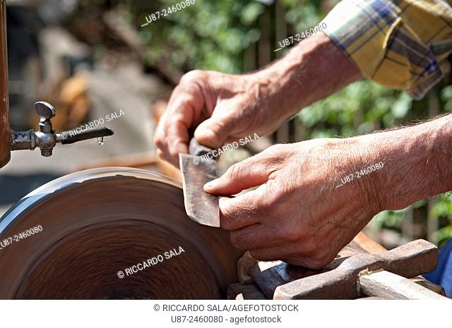 Italy, Lombardy, Knife Sharpener Grinding a Blade. . .