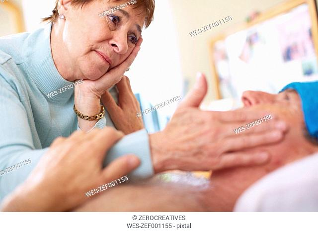 Senior woman caring for sick husband at home