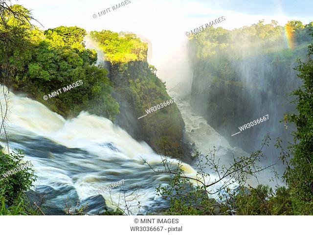 High angle view of waterfall cascading down overgrown rocks, single rainbow