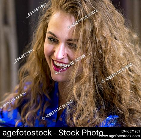 A smiling 28 year old woman with long blond hair