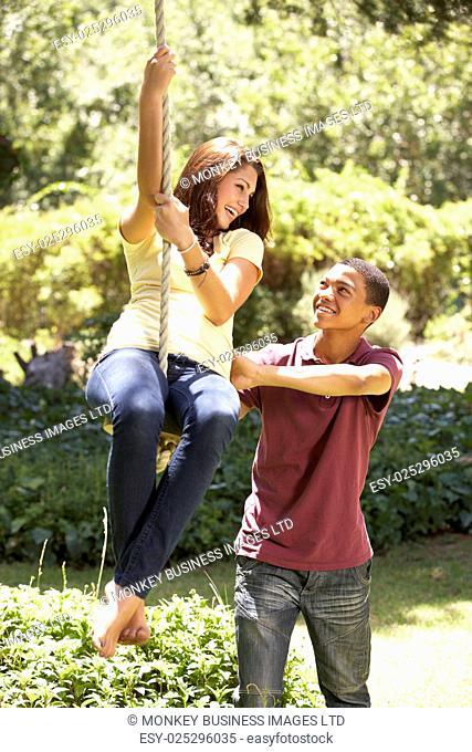 Teenage Couple Having Fun On Rope Swing