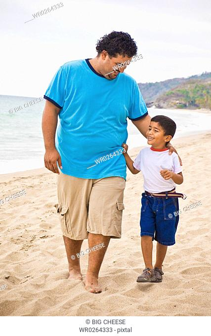 young mexican father and son on beach