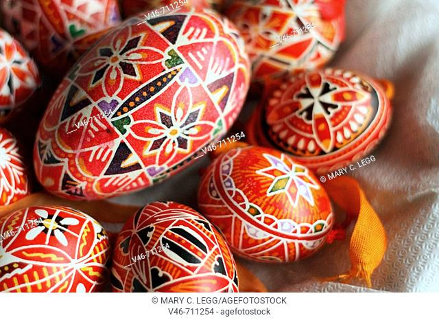 A half basket of  red hand-painted Czech Easter eggs. A large goose egg hand-painted in red and black abstract geometrical  pattern is  surrounded by  small...