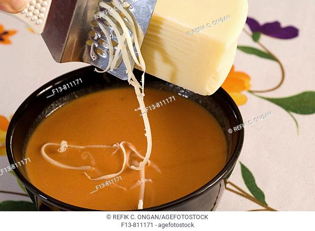 Shaving cheese into tomatoes soup