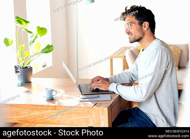 Man wearing eyeglasses looking away while sitting with laptop at home office